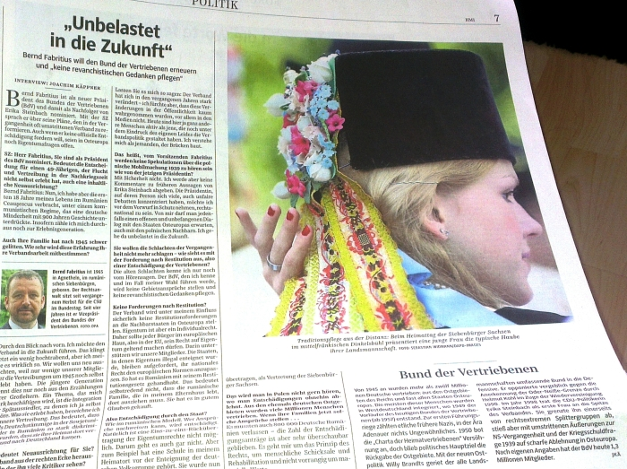 """Sașii în Germania:  pagina 7 a """"Süddeutsche Zeitung"""" din 10.07.2014, cu imaginea unei tinere săsoaice prezentând Borten-ul (toca de catifea neagră împodobită, purtată de fete de la confirmare la căsătorie) la Întâlnirea sașilor de la Dinkelsbühl 2014. Un interviu cu dr Bernd Fabritius, Președintele Asociației Sașilor Transilvăneni, recent nominalizat la președinția Uniunii Etnicilor Germani Expatriați/Bund der Vertriebenen (BdV), ocupată până acum de Erika Steinbach. Probabil articolul va fi disponibil și online în curând."""