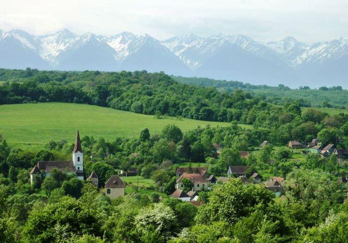 Văzut din depărtare, Gherdealul e o gură de rai, ocrotită de păduri și culmile înzăpezite ale munților. De aproape, e un sat-fantomă. Sursa foto: gherdeal.blogspot.com.